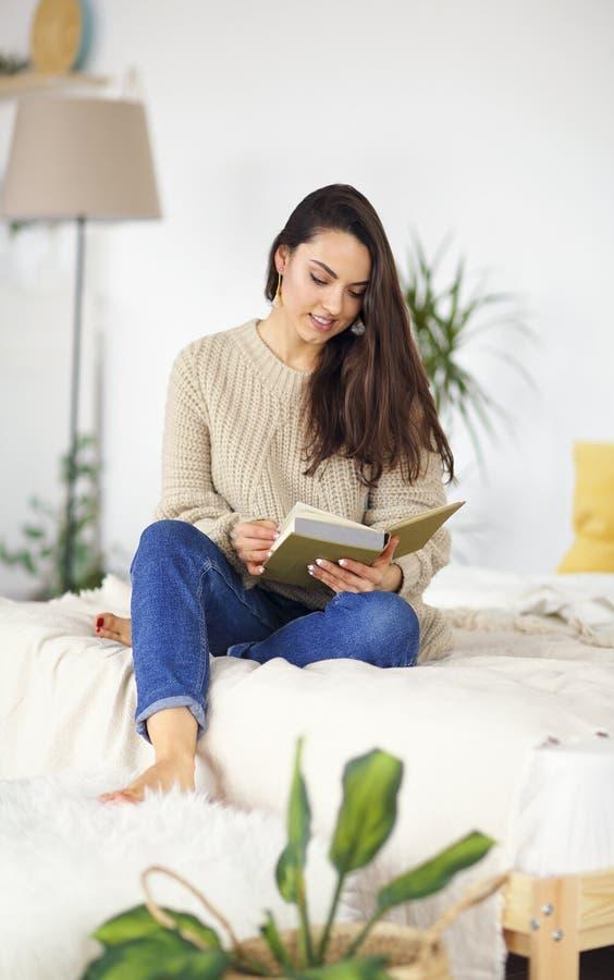 Jeune femme heureuse de brune avec le chandail de port de livre photo stock