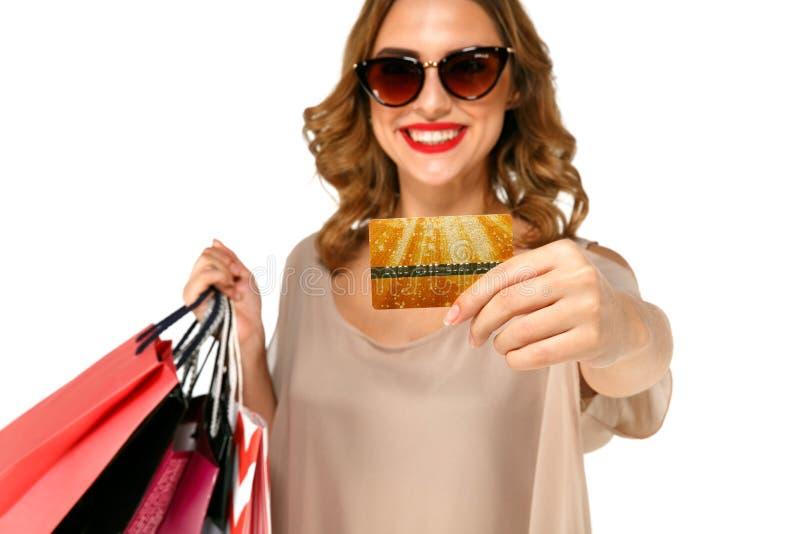 Jeune femme heureuse de brune dans des lunettes de soleil tenant la carte de crédit d'or et les paniers colorés photos stock