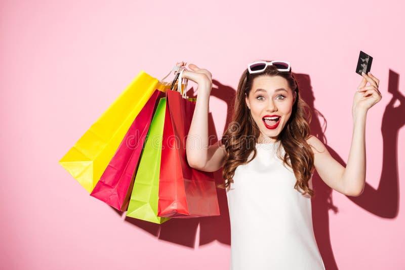 Jeune femme heureuse de brune tenant la carte de crédit et les paniers photo libre de droits