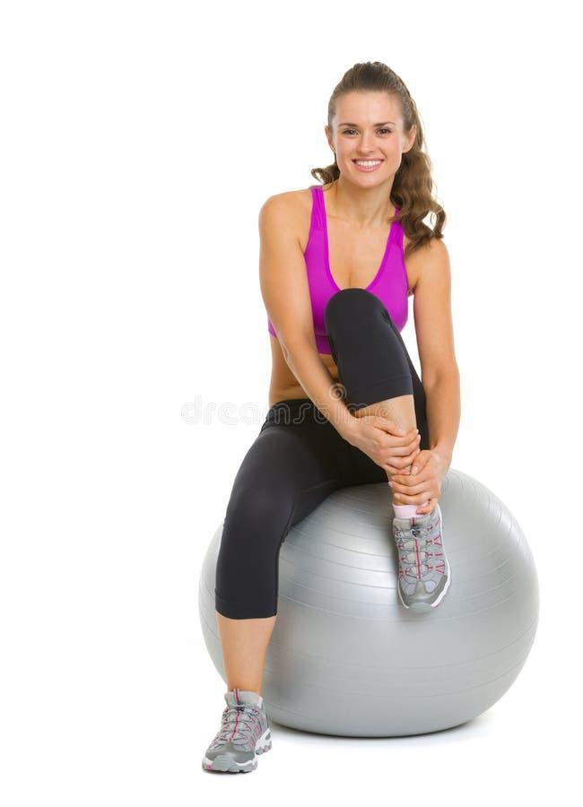 Jeune femme heureuse de forme physique s'asseyant sur la boule de forme physique photographie stock libre de droits