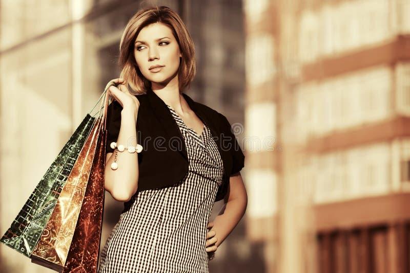 Jeune femme heureuse de mode avec des paniers au mail image stock
