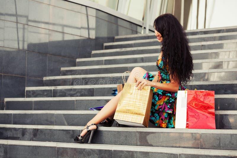 Jeune femme heureuse de mode avec des paniers se reposant sur des étapes photos libres de droits