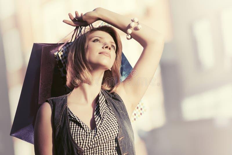 Jeune femme heureuse de mode avec des paniers sur la rue de ville photos stock