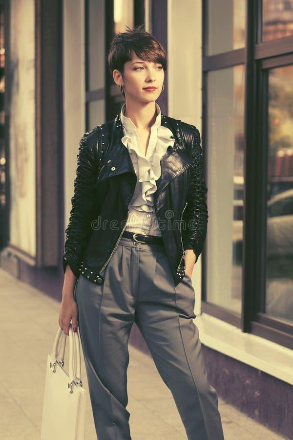 Jeune femme heureuse de mode dans la veste en cuir avec le sac ? main photographie stock