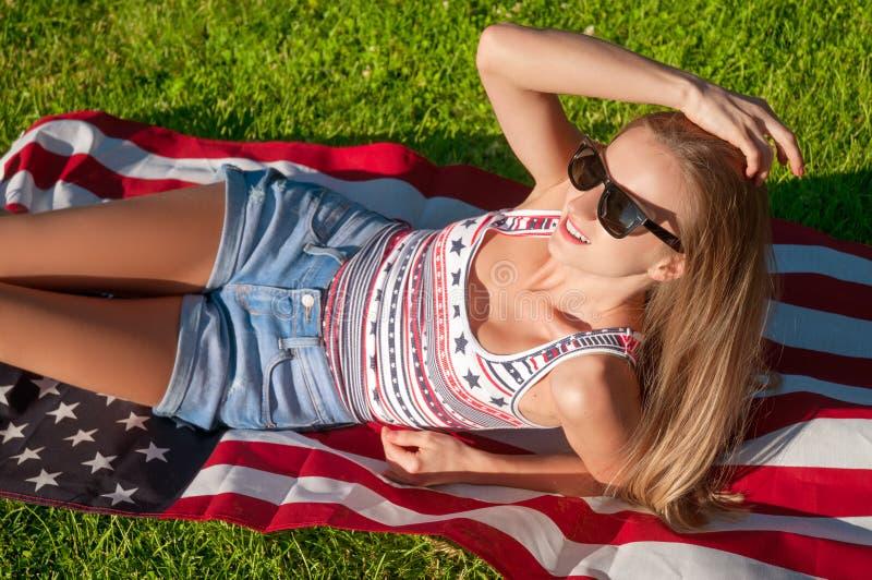 Jeune femme heureuse de patriote tenant le drapeau des Etats-Unis images libres de droits