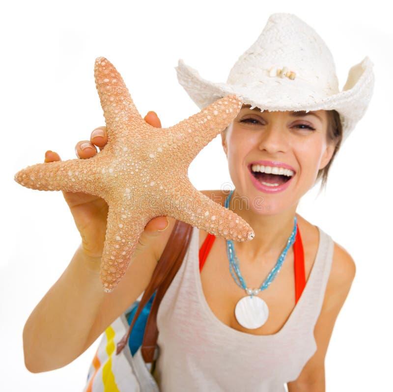Jeune femme heureuse de plage dans le chapeau montrant des étoiles de mer photos libres de droits