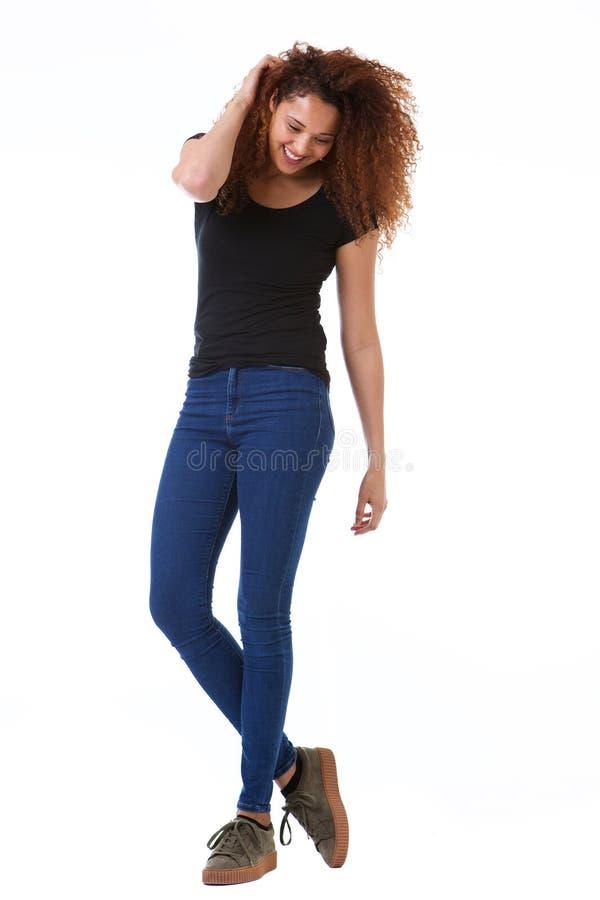 Jeune femme heureuse de plein corps avec la main dans les cheveux bouclés se tenant sur le fond blanc d'isolement photos stock