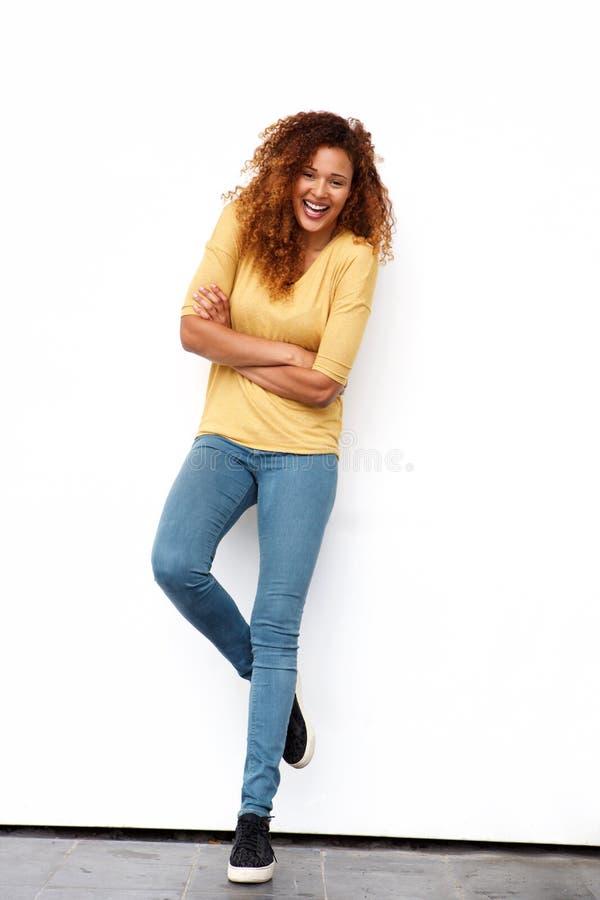 Jeune femme heureuse de plein corps avec les cheveux bouclés contre le mur blanc image stock