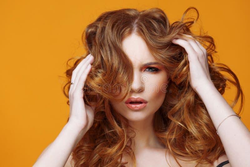Jeune femme heureuse de roux avec les cheveux bouclés luxueux Portrait de studio sur le fond jaune Excellents cheveux photo libre de droits