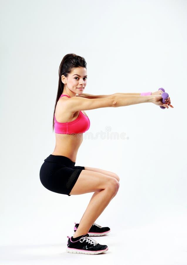 Jeune femme heureuse de sport faisant des postures accroupies avec des haltères photos libres de droits