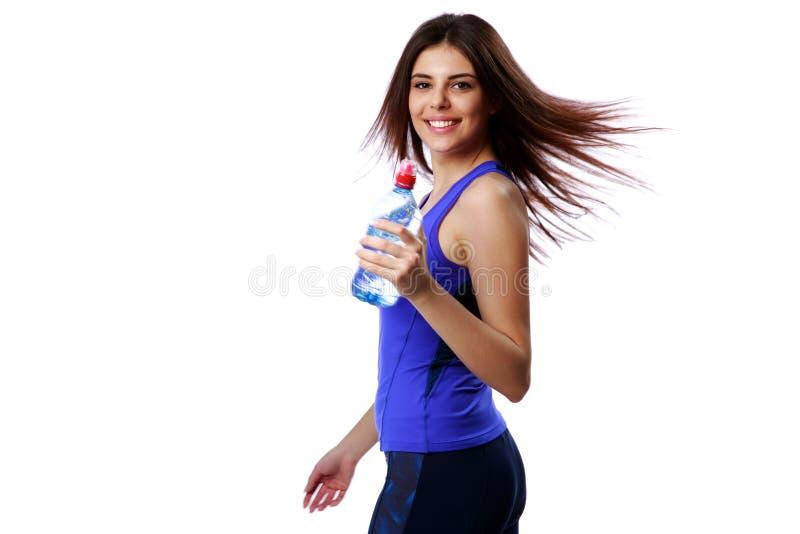 Jeune femme heureuse de sport tenant la bouteille avec de l'eau images stock