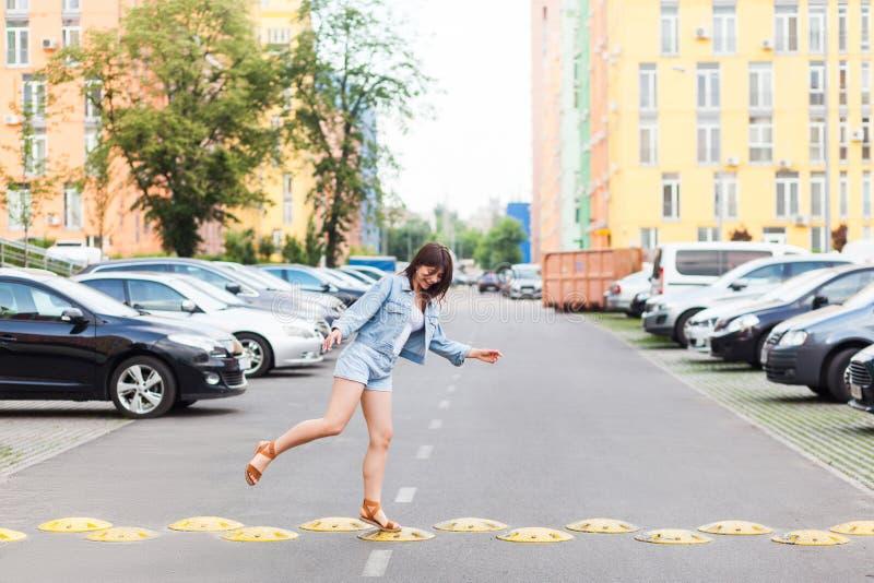 Jeune femme heureuse drôle dans le style occasionnel de denim bleu sautant et marchant sur la bosse jaune de ville de route le jo images stock