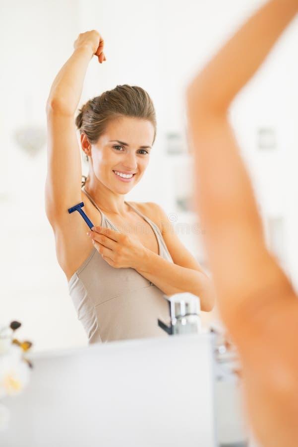 Jeune femme heureuse employant rasant l'aisselle dans la salle de bains photo stock