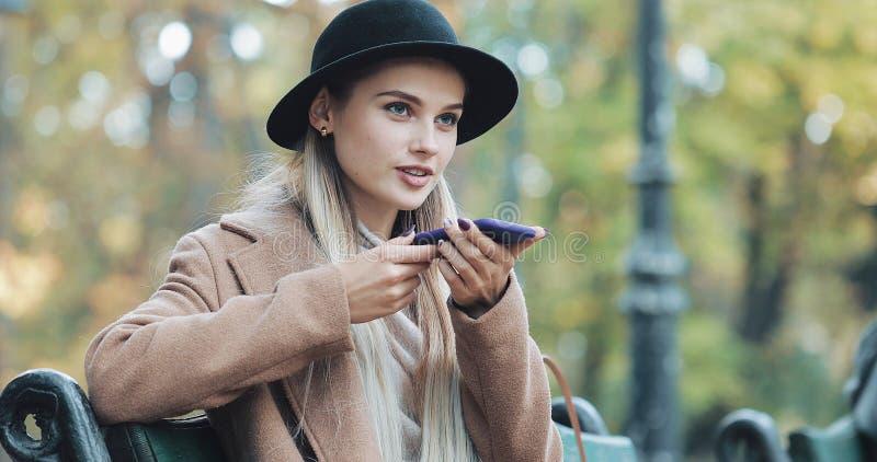 Jeune femme heureuse employant une fonction de reconnaissance vocale de smartphone Elle s'asseyant sur le banc en parc et ordres  image stock