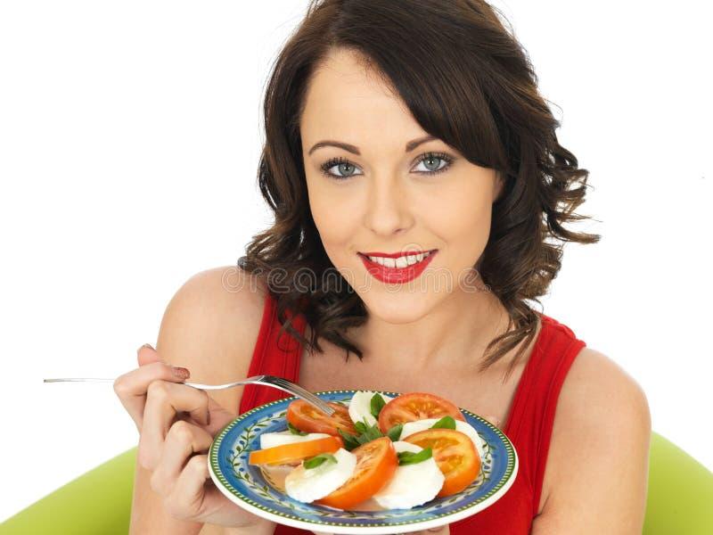 Jeune femme heureuse en bonne santé mangeant d'une salade de fromage et de tomate de mozzarella photographie stock