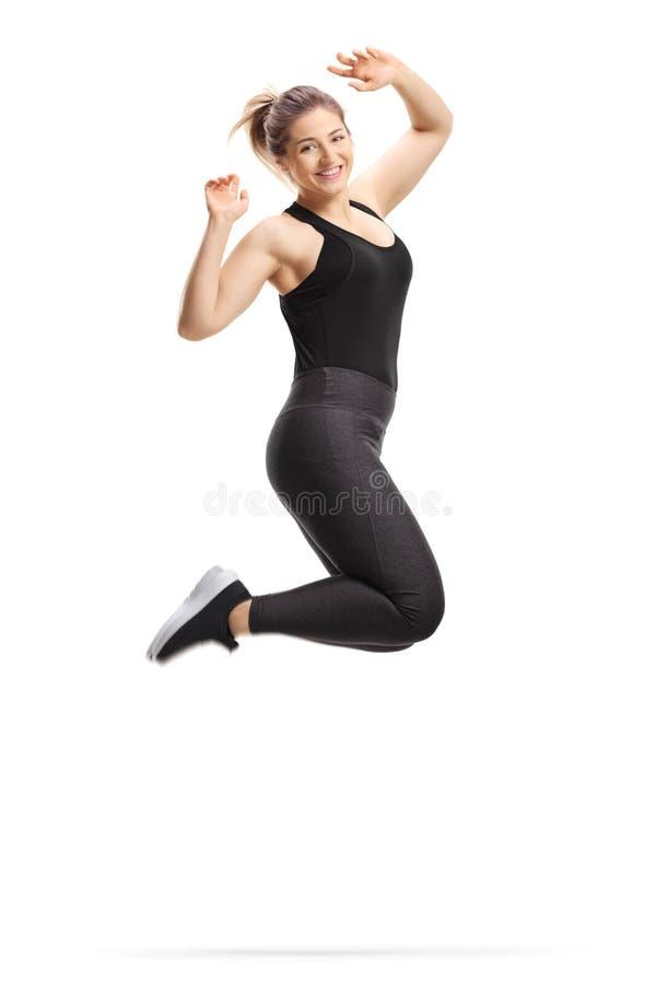Jeune femme heureuse en sportswear, saut et sourire photos libres de droits