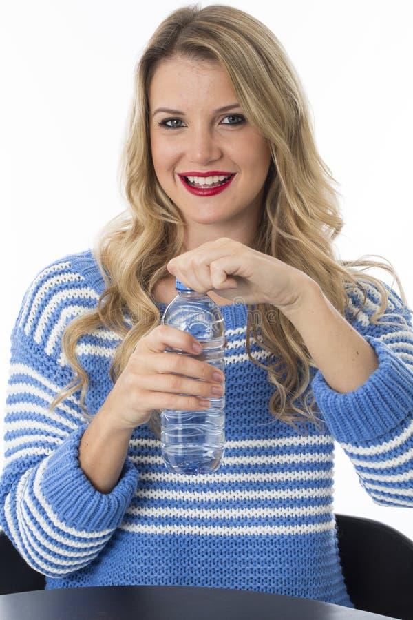 Jeune femme heureuse enlevant le couvercle de la bouteille de l'eau minérale images stock