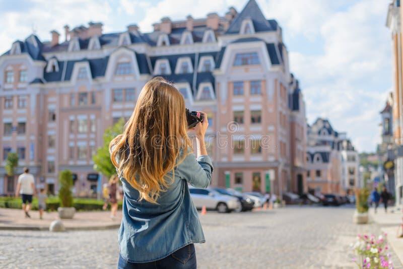 Jeune femme heureuse, enthousiaste, élégante rapportant la photo du point de repère au bel arrière euripean nouveau vieux de vill photographie stock libre de droits