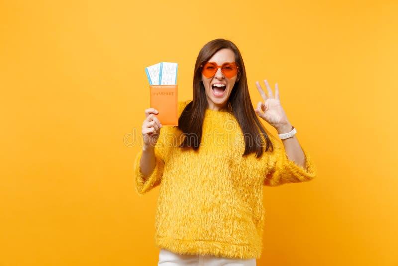 Jeune femme heureuse enthousiaste en verres oranges de coeur montrant des billets de passeport et de carte d'embarquement de part image stock