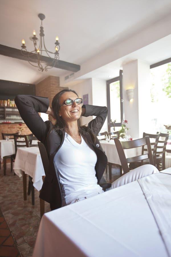 Jeune femme heureuse et jolie s'asseyant dans un restaurat photo stock