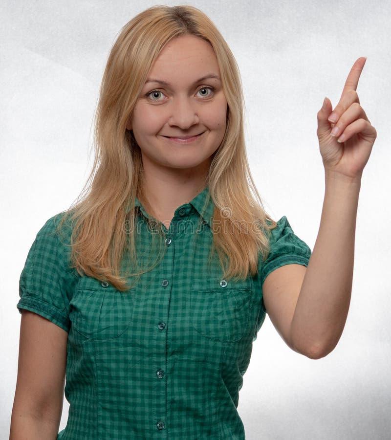 Jeune femme heureuse et souriante dans la chemise verte occasionnelle se dirigeant et regardant directement dans la caméra image libre de droits