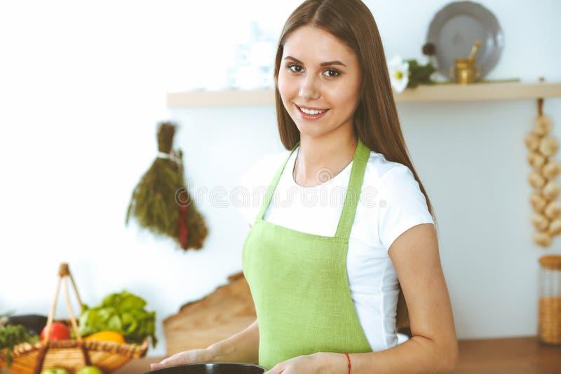 Jeune femme heureuse faisant cuire la soupe dans la cuisine Repas sain, mode de vie et concept culinaire Fille de sourire d'?tudi image stock