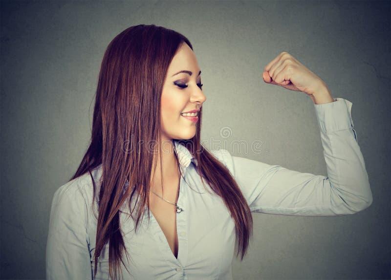 Jeune femme heureuse fléchissant des muscles lui montrant la puissance photographie stock