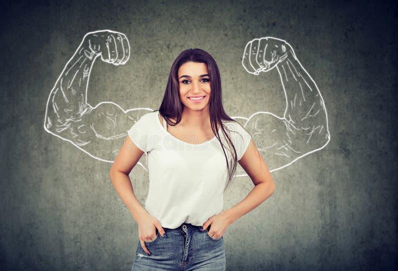 Jeune femme heureuse forte fléchissant ses muscles photo libre de droits