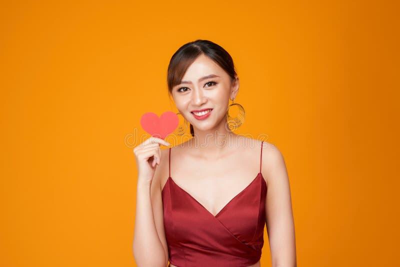 Jeune femme heureuse habillée dans la robe rouge tenant le coeur de papier au-dessus du fond jaune photos libres de droits