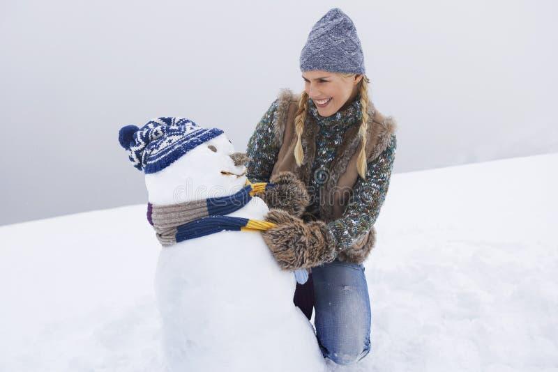 Jeune femme heureuse habillant le bonhomme de neige images stock