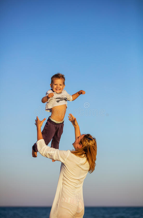 Jeune femme heureuse jetant le petit fils en air sur la plage image libre de droits