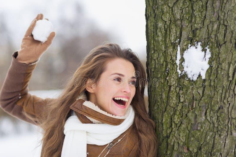 Jeune femme heureuse jouant dans des combats de boule de neige image libre de droits