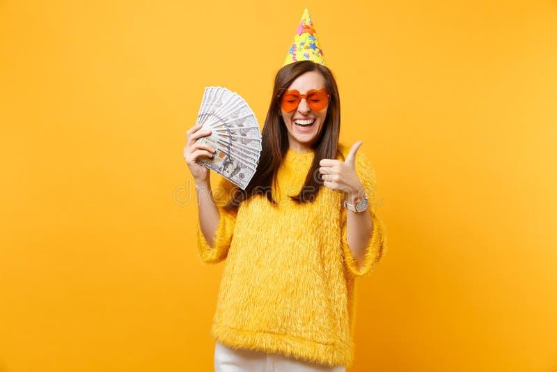 Jeune femme heureuse joyeuse dans le pouce orange d'apparence de chapeau d'anniversaire en verre de coeur vers le haut de tenir u photos libres de droits