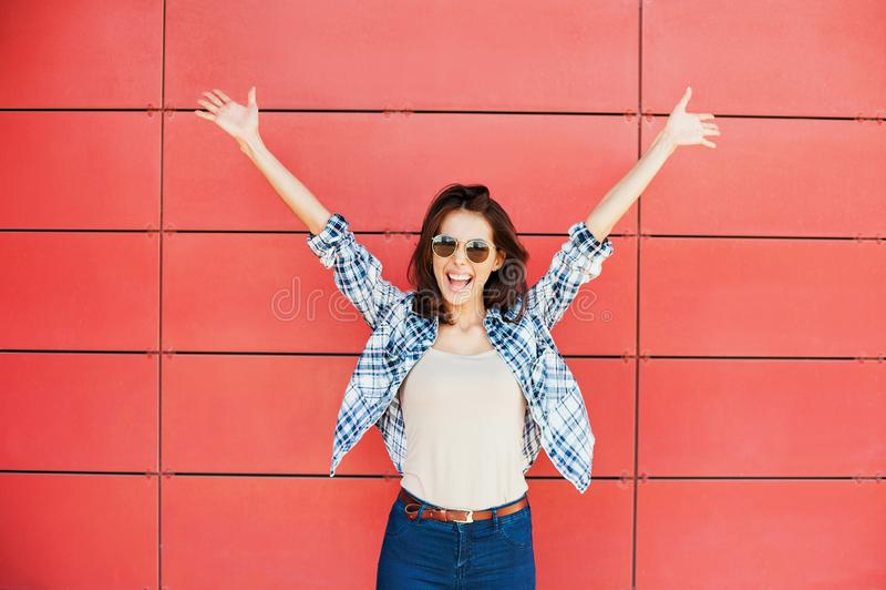 Jeune femme heureuse joyeuse sautant contre le mur rouge Beau portrait enthousiaste de fille images libres de droits