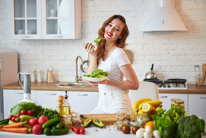 Jeune femme heureuse mangeant de la salade dans la belle cuisine avec les ingrédients frais verts à l'intérieur Concept sain de n image stock