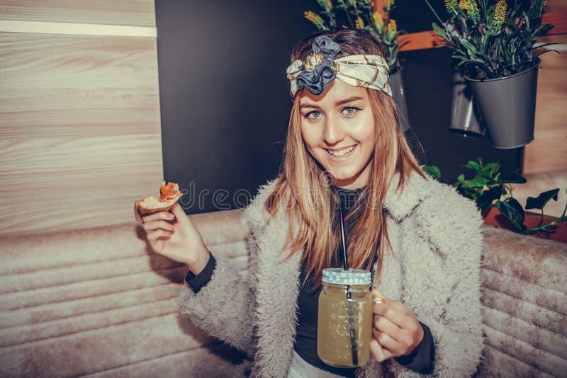 Jeune femme heureuse mangeant une tranche de pizza et buvant de la limonade image stock