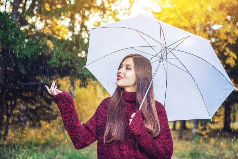 Jeune femme heureuse marchant dans Sunny Park avec un parapluie blanc sous la pluie Concept des saisons et de l'humeur d'automne photographie stock