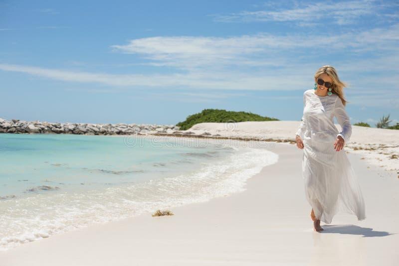 Jeune femme heureuse marchant sur la plage images stock