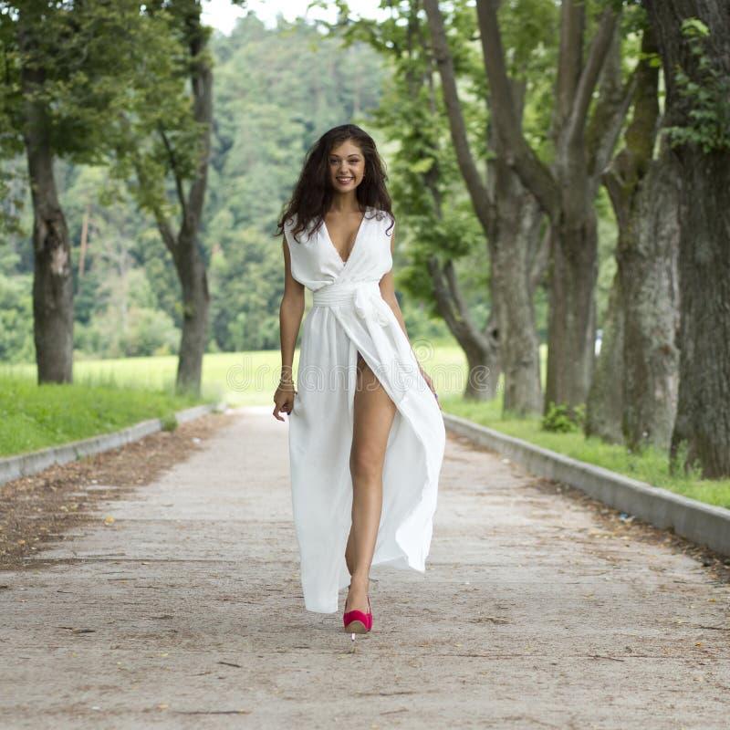 Jeune femme heureuse marchant sur le parc d'été image stock