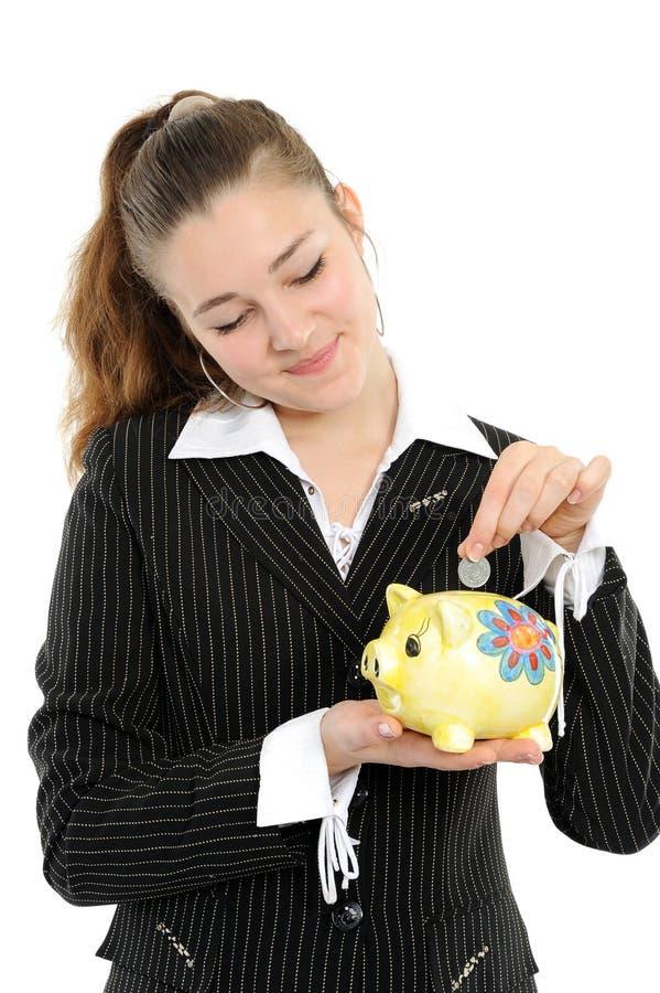 Jeune femme heureuse mettant l'argent dans le piggybank photo libre de droits