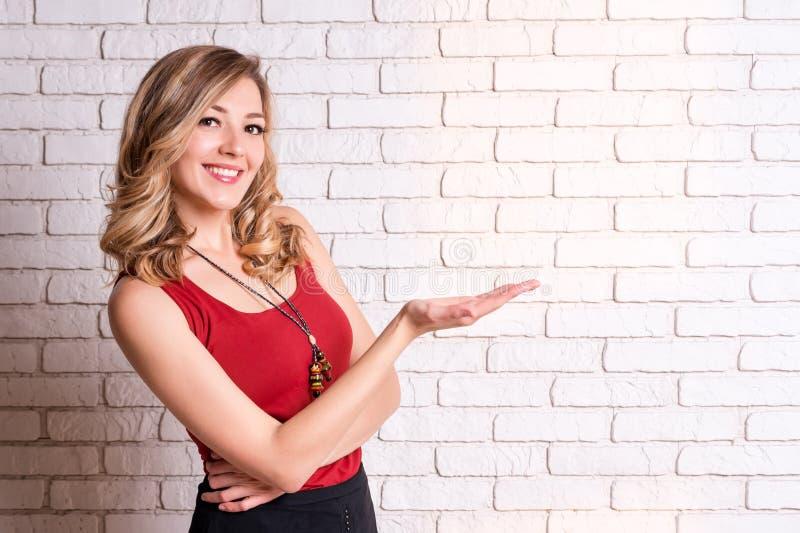 Jeune femme heureuse montrant le pointage de copyspace Jeune femelle blonde dirigeant des doigts loin L'espace de copie pour votr photos libres de droits
