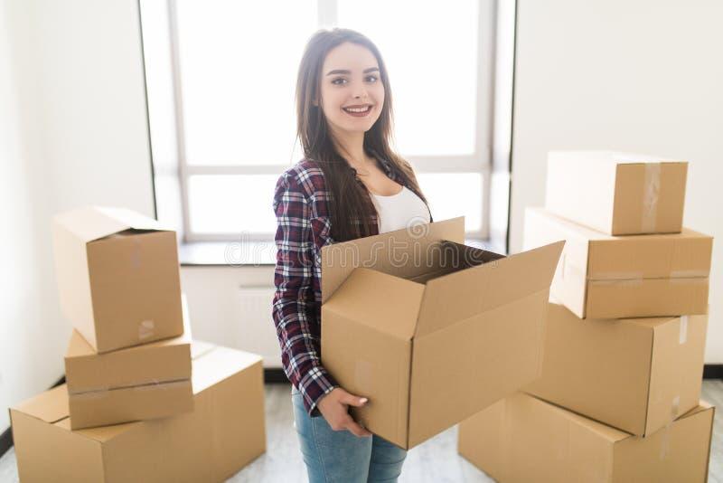 Jeune femme heureuse portant une pile des boîtes en carton dans son nouveau hause, elle sourit à l'appareil-photo images stock