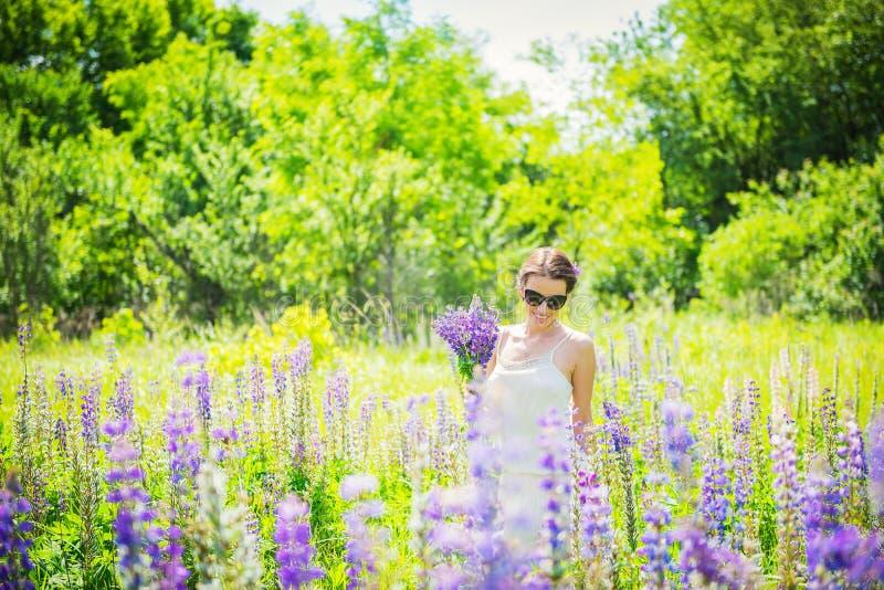 Jeune femme, heureuse, position parmi le champ des lupines violets, souriant, fleurs pourpres Ciel bleu sur le fond Été, avec photographie stock libre de droits