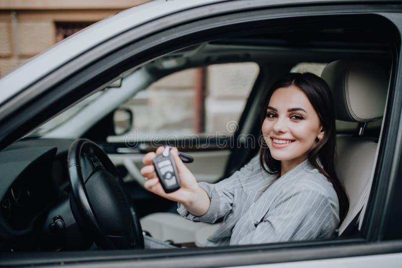 Jeune femme heureuse près de la voiture avec des clés à disposition Concept de voiture de achat image libre de droits