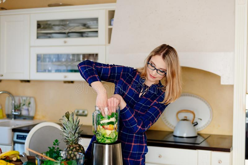 Jeune femme heureuse préparant le cocktail de smoothie dans le mélangeur photo libre de droits