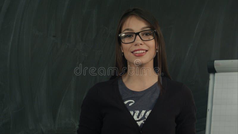 Jeune femme heureuse présentant l'exposé d'affaires dans le bureau photos stock