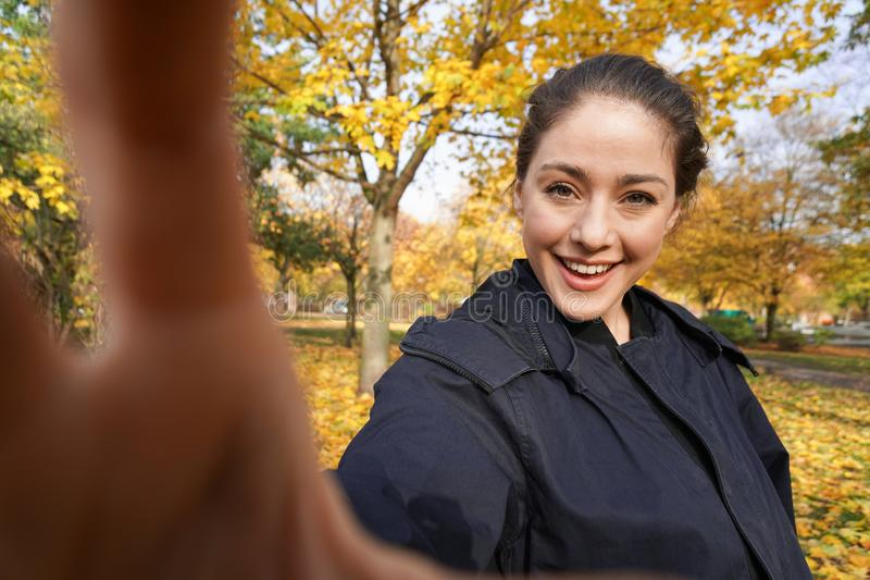 Jeune femme heureuse prenant la photo de selfie en parc avec des couleurs d'automne images stock