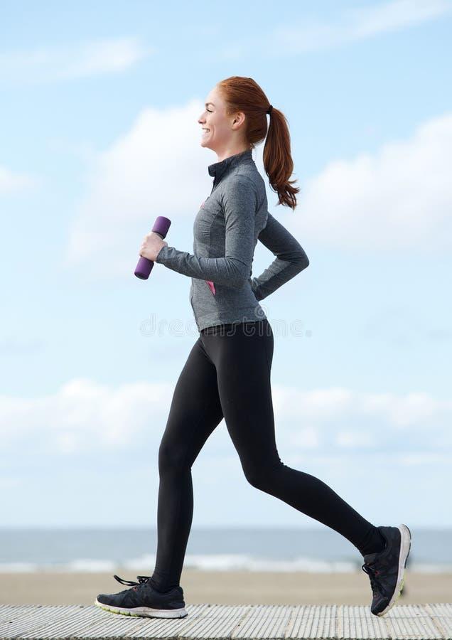 Jeune femme heureuse pulsant avec des poids photo libre de droits