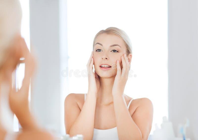 Jeune femme heureuse regardant pour refléter à la salle de bains image stock