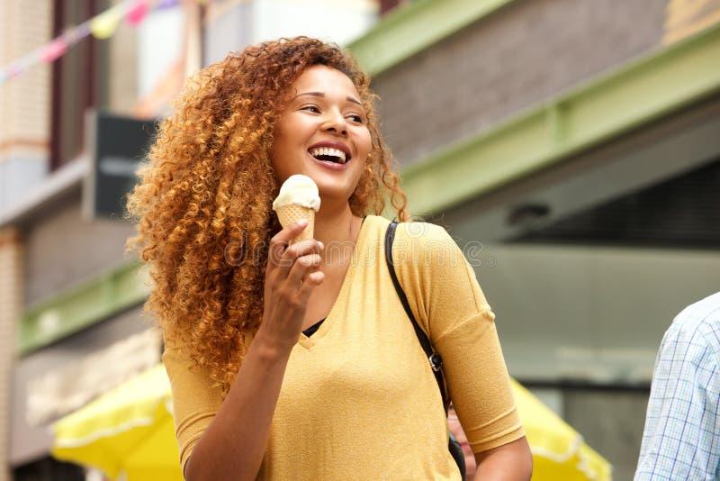Jeune femme heureuse riant avec la crème glacée dans la ville image stock